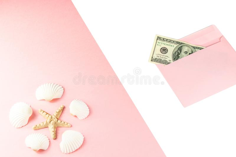 Travel budget. Money in a pink envelope, starfish, seashells on a blue background. Copy space, top view. Travel budget. Money in a pink envelope, starfish stock photos