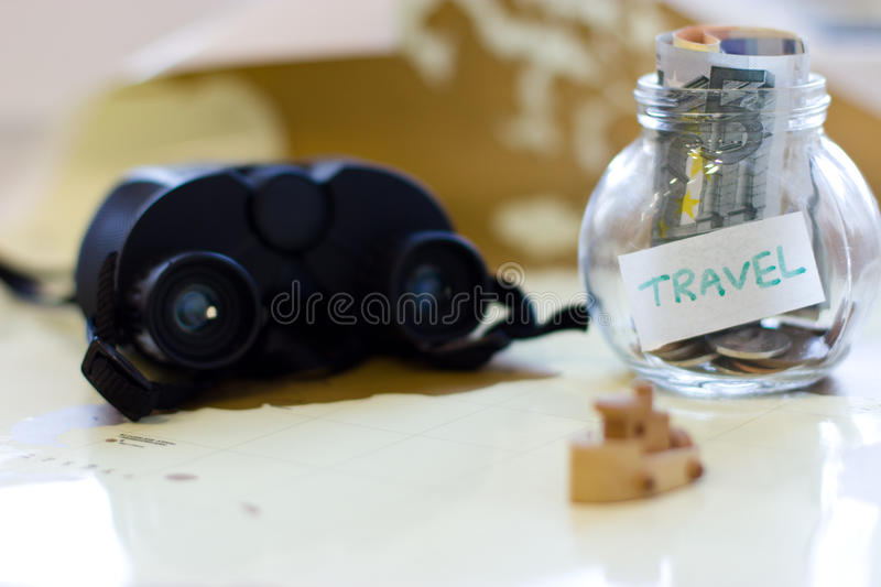 Travel budget - vacation money savings in a glass jar on world m. Ap. Collecting money for travel royalty free stock photos