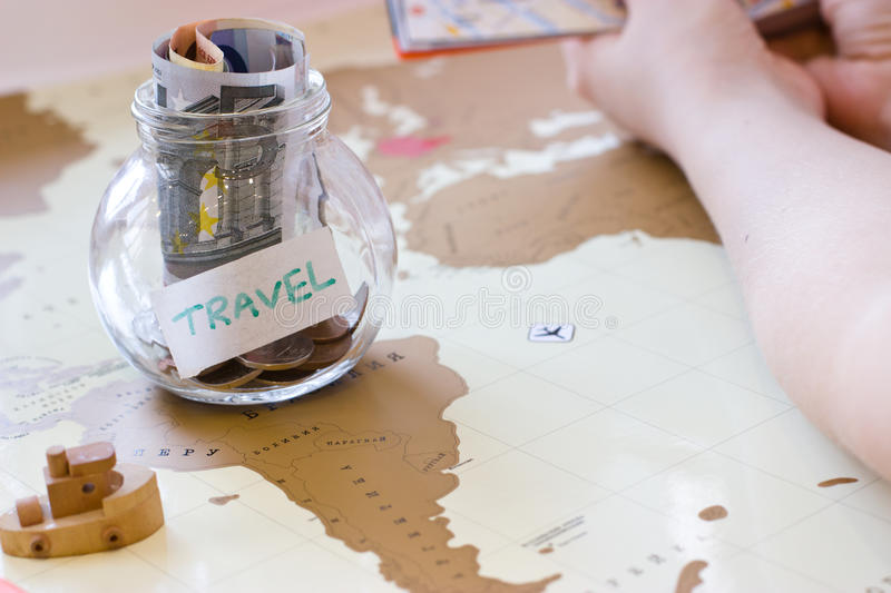Travel budget - vacation money savings in a glass jar on world m. Ap. Small wooden boat. Hand in the guide royalty free stock image