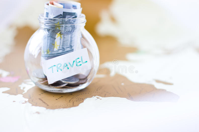 Travel budget - vacation money savings in a glass jar. On world map royalty free stock photography
