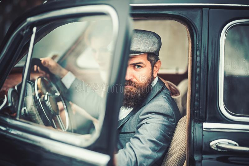 Travel and business trip or hitch hiking. Couple in love on romantic date. Bearded man and sexy woman in car. Retro royalty free stock image