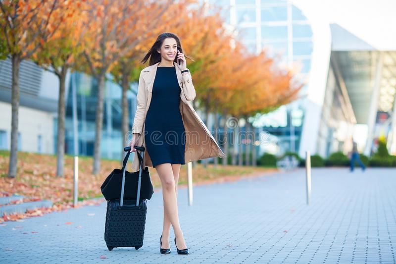 Travel. Business Woman in airport talking on the smartphone while walking with hand luggage in airport going to gate stock image