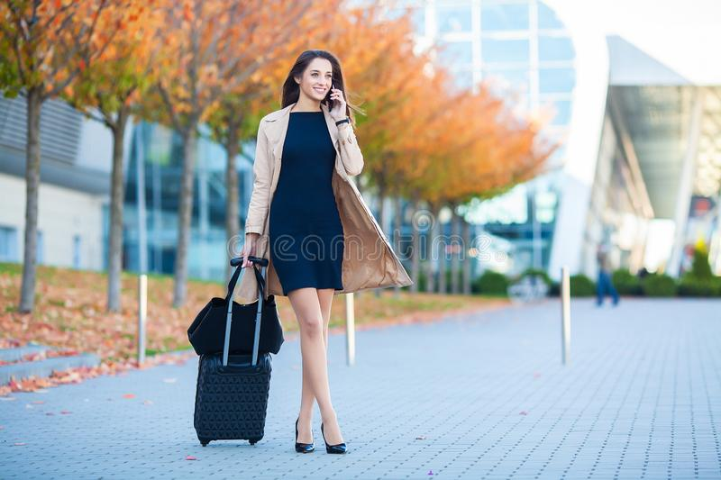 Travel. Business Woman in airport talking on the smartphone while walking with hand luggage in airport going to gate royalty free stock photos