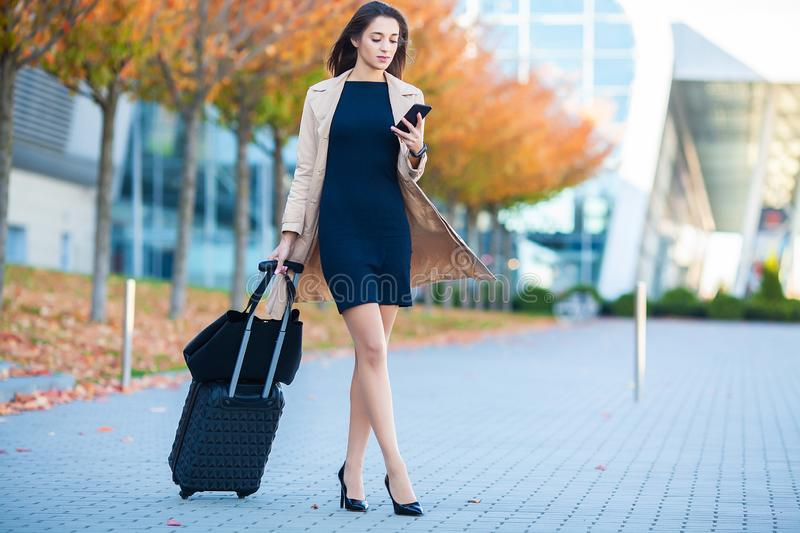 Travel. Business Woman in airport talking on the smartphone while walking with hand luggage in airport going to gate stock photos