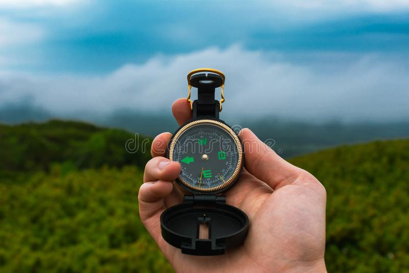 Travel, camping, orienteering and navigation concept - black magnetic compass close-up in a man s hand, blurred landscape royalty free stock photo
