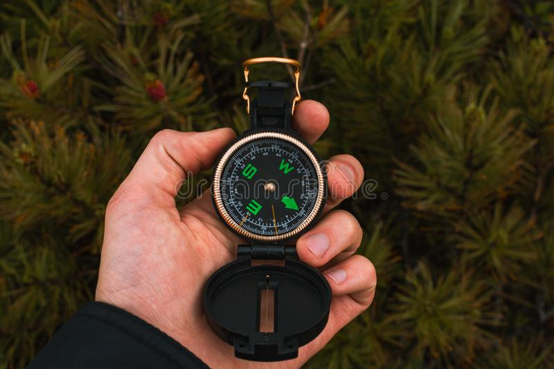 Travel, camping, orienteering and navigation concept - black magnetic compass close-up in a man s hand, pine branches background. Discovery, direction, arrow royalty free stock images