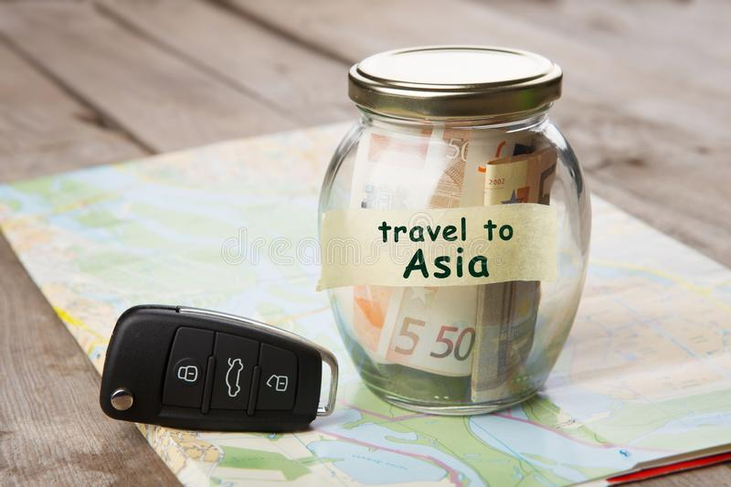 Travel by car to Asia - money jar, car key and roadmap. Rent, auto, rental, sale, security, driving, insure, buy, alarm, vehicle, service, business, open stock photo