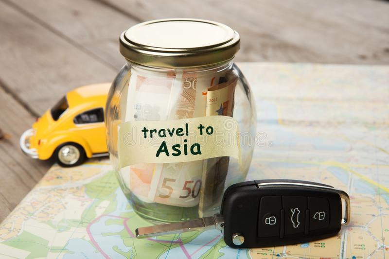 Travel by car to Asia - money jar, car key. And roadmap, rent, auto, rental, sale, security, driving, insure, buy, alarm, vehicle, service, business, open royalty free stock image