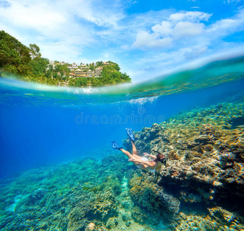 Travel card with a woman floating on a background of green islands. And coral reef in the foreground royalty free stock photography