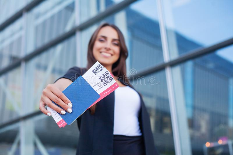 Travel. Cheerful young woman holding plane tickets outdoors royalty free stock image
