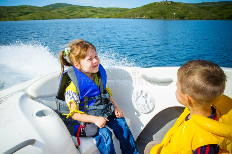 Travel of children on water in the boat. Two kids sitting in the bow of a boat with there life jackets having fun stock image