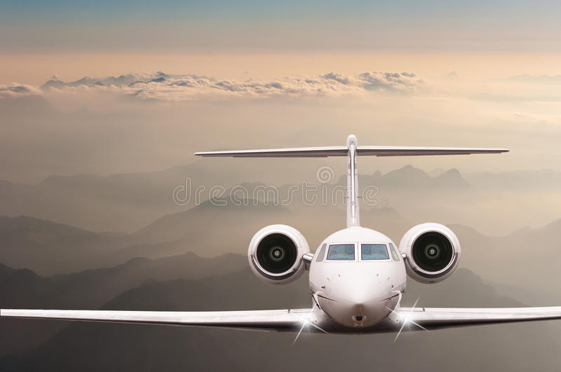 Travel concept. Airplane fly over clouds and Alps mountain on sunset. Front view of a big passenger or cargo aircraft. Business jet, airline. Empty space for royalty free stock images