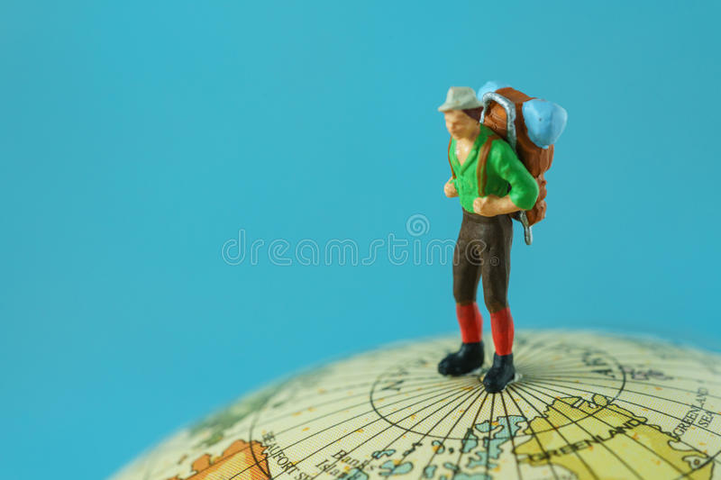 Travel concept as a miniature figure young man with backpack sta stock photos