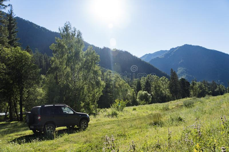 Travel concept with big 4x4 car against sunset and mountains. photo of offroad wheel. Travel concept with big 4x4 car against sunset and mountains. photo of stock images
