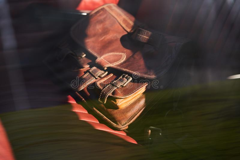 Travel concept with brown leather bag on old car seat royalty free stock photos