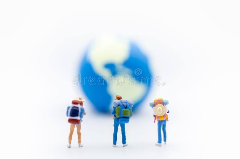 Travel Concept. Close up of group of traveler miniature figure with backpack standing on white background with mini world ball and. Copy space royalty free stock photography
