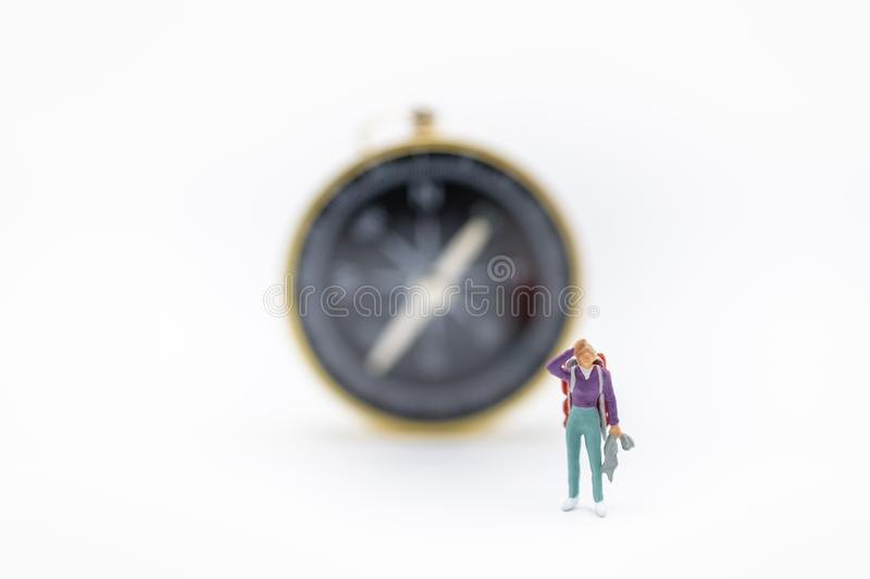 Travel Concept. Close up of traveler miniature figure with backpack and jacket standing with compass on white background and copy royalty free stock photos