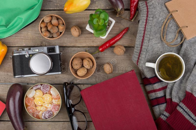 Travel concept - cup of tea, sweater, camera, book, eyeglasses, vegetables, nuts, candies. Accessories, spring, autumn, trip, pullover, background, brown, cafe royalty free stock images