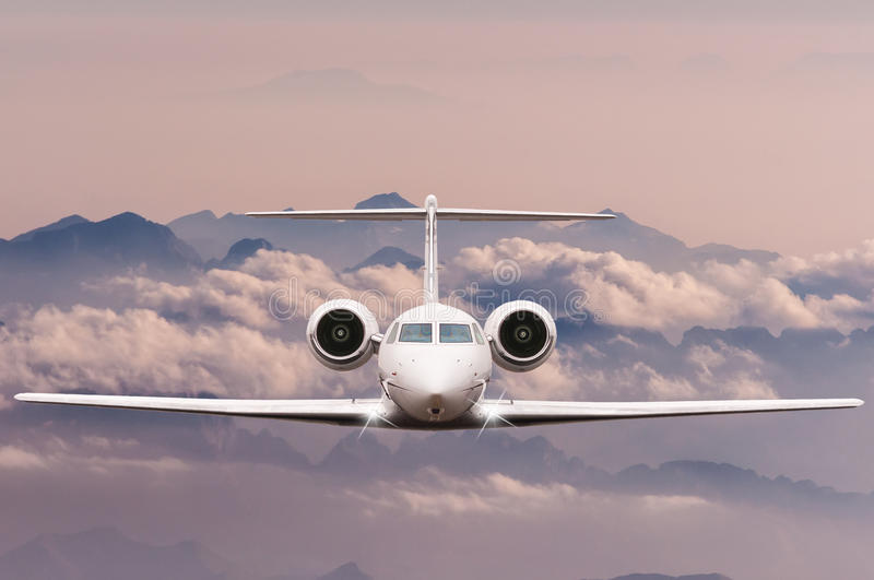 Travel concept. Front view of Jet airliner in flight with sky, cloud and mountain background. Commercial passenger or. Front view of jet airliner in flight with royalty free stock photo