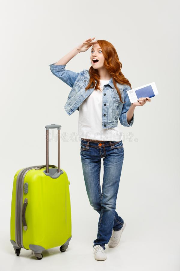 Travel Concept: Full-length young happy surprised beautiful woman holding green suitcase over white background stock photo