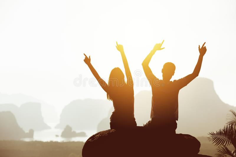 Happy couple with raised arms at mountains and islands sunrise royalty free stock photo