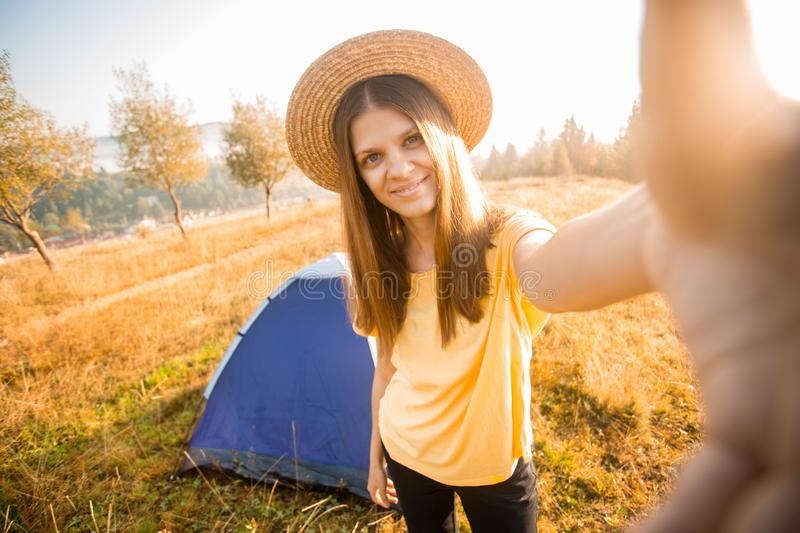 Happy woman in hat take selfie with camera after wake up in tent in autumn morning stock photography
