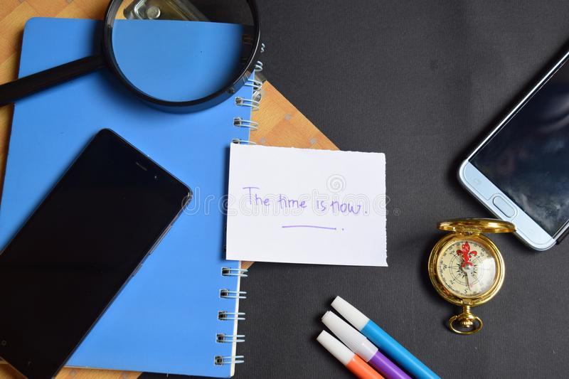 The time is now written on paper. magnifying glass, Compass, Smartphone. Travel Concept Inspiration - the time is now written on paper. magnifying glass, Compass royalty free stock photo