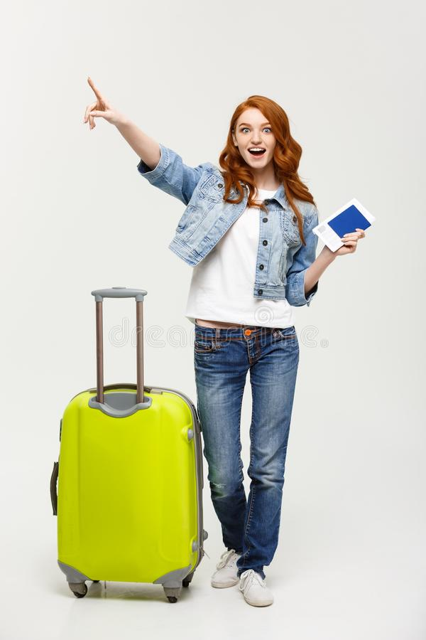 Travel Concept: Portrait of a cheerful young caucasian woman casual dress holding passport with flying tickets while royalty free stock photography