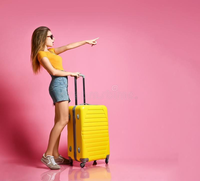 Portrait of a cheerful young caucasian woman dressed in summer clothes, with a suitcase and pointing finger away royalty free stock photo