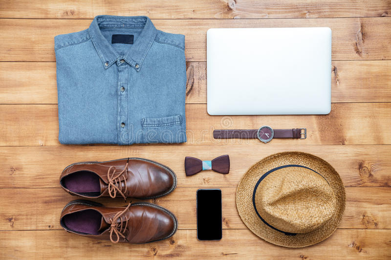 Travel concept shoes, shirt, mobile phone, watch, laptop, hat. On the desk royalty free stock photography