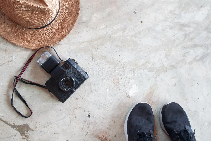 Travel concept with straw hat, camera and shoes on concrete floor. Flat lay royalty free stock image