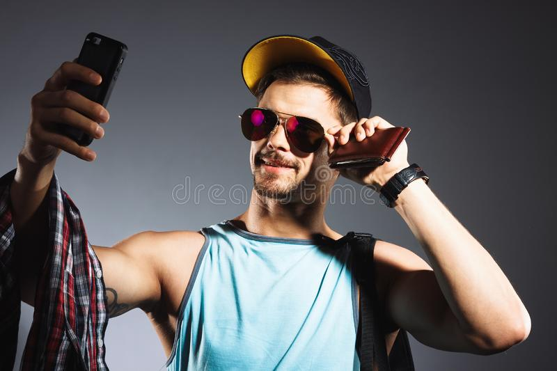 Travel concept. Studio portrait of handsome young man taking selfie. Studio portrait of handsome young student in sunglasses taking photo on his phone stock photo