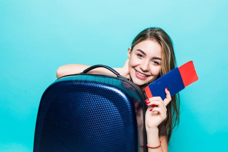 Travel concept. Portrait of pretty young woman holding passport with suitcase and thinking about something on blue background. Travel concept. Studio portrait of royalty free stock images