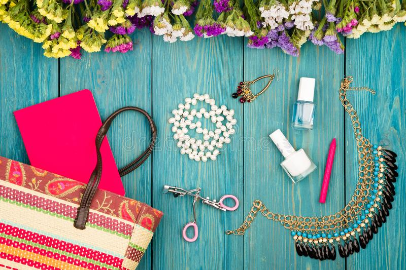 Straw bag, colorful flowers, cosmetics makeup, notepad, bijou and essentials on blue wooden background. Travel concept - summer women set with straw bag royalty free stock photography