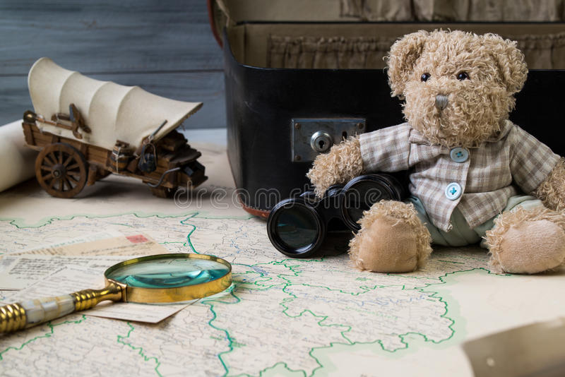 Travel concept, teddy bear with old binoculars and suitcase on the antique map with magnify glass royalty free stock image