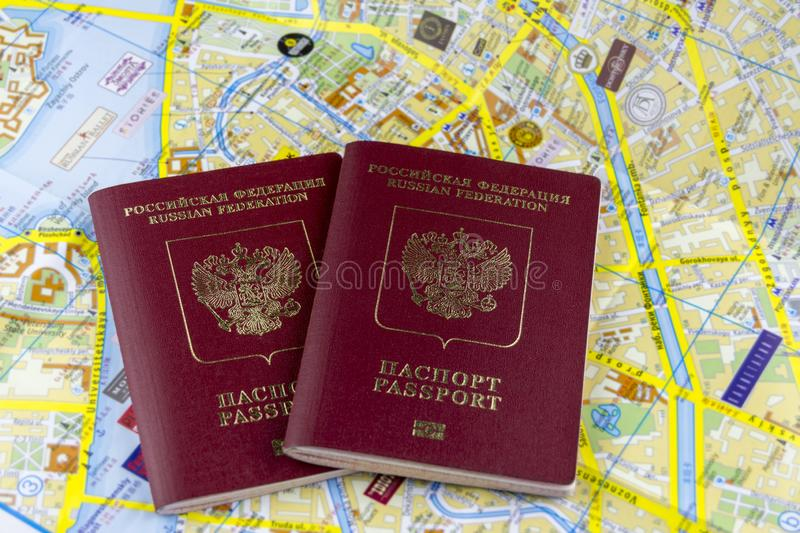 Travel concept. Two Russian passports on the background of a paper map of the city stock image