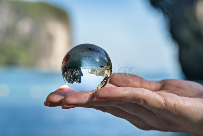 Travel concept, woman holding glass crystal ball royalty free stock photography
