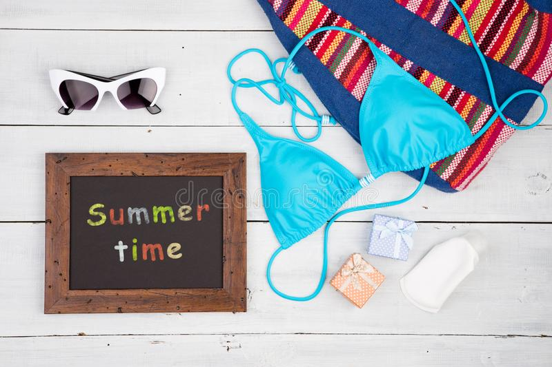 Blue swimsuit, striped bag, sunglasses, sunscreen, gift boxes and signboard with inscription & x22;Summer time& x22;. Travel concept - women& x27;s fashion with stock photography