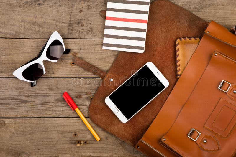 women set with bag, smart phone, sunglasses, notepad, pen and purse on brown wooden desk royalty free stock photos
