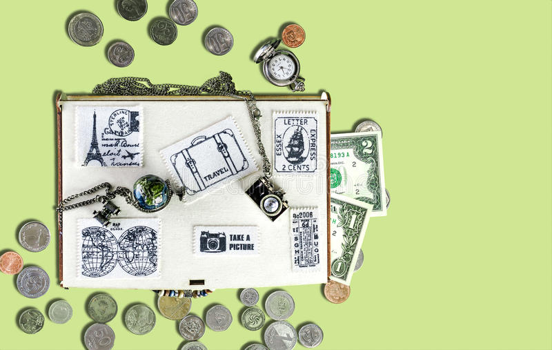 Travel concept: Wooden travel box with stickers of fabric, banknotes and coins, watches, metal pendants in the form of. Wooden travel box with stickers of fabric stock photography