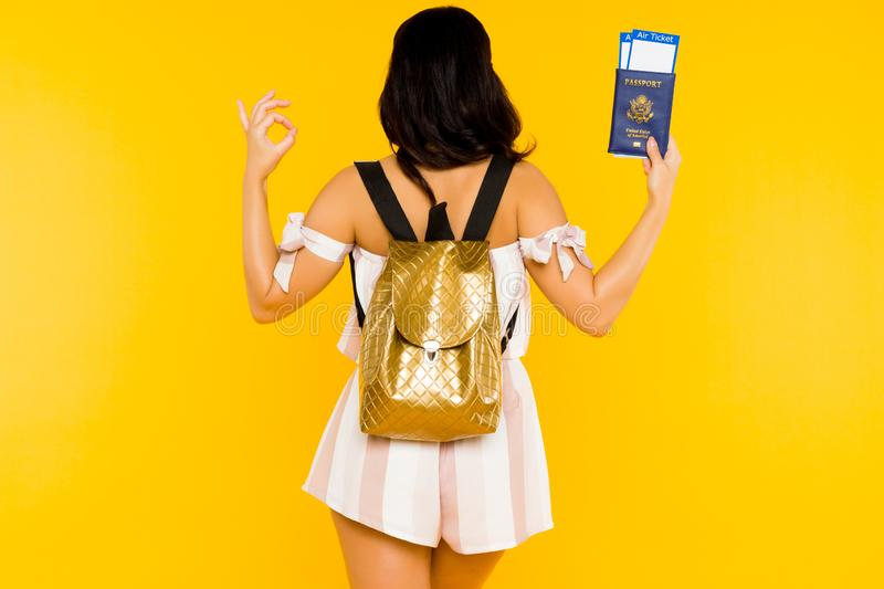 Travel concept. Young asian woman holding passport with tickets standing back with knapsack shows ok sign royalty free stock image