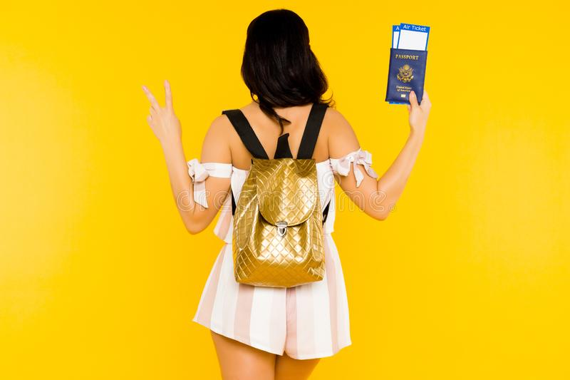 Travel concept. Young asian woman holding passport with tickets standing back with knapsack shows peace sign stock images