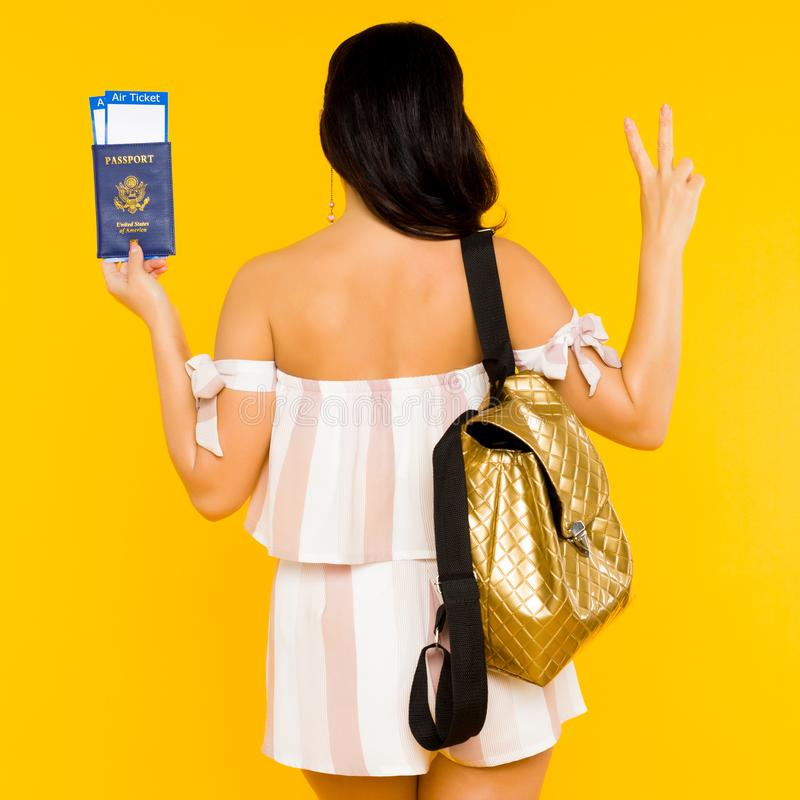 Travel concept. Young asian woman holding passport with tickets standing back with knapsack shows peace sign stock photos