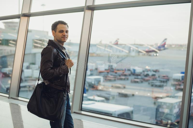Travel concept with young man in airport interior with city view and a plane flying by. Travel concept with young man in airport interior with city view and a stock photo