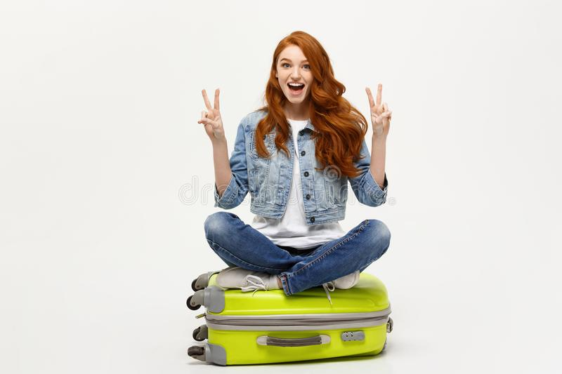 Travel concept: young smiling caucasian woman siting on suitcase showing two fingers. Isolated over white background. royalty free stock photography