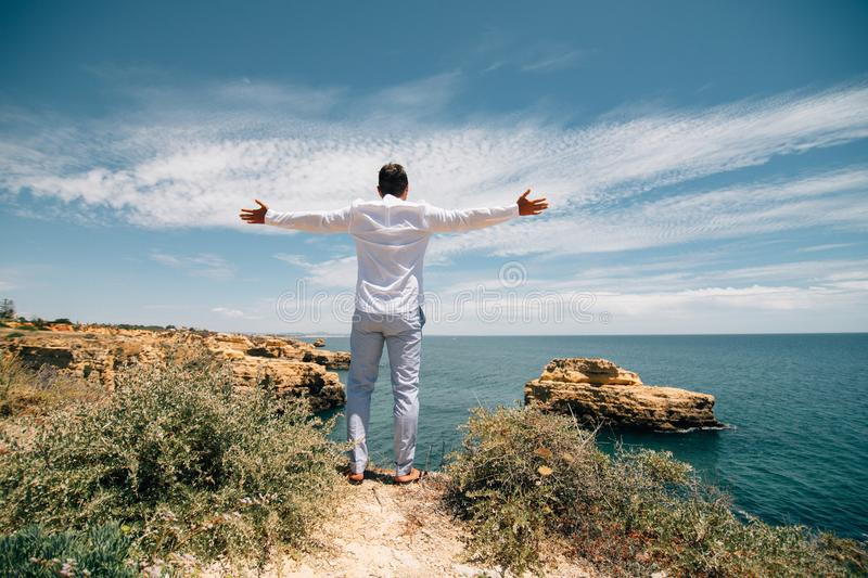 Travel concept. Young tourist man standing on the edge of reef enjoying ocean or sea view of turquoise water with raised hands royalty free stock images