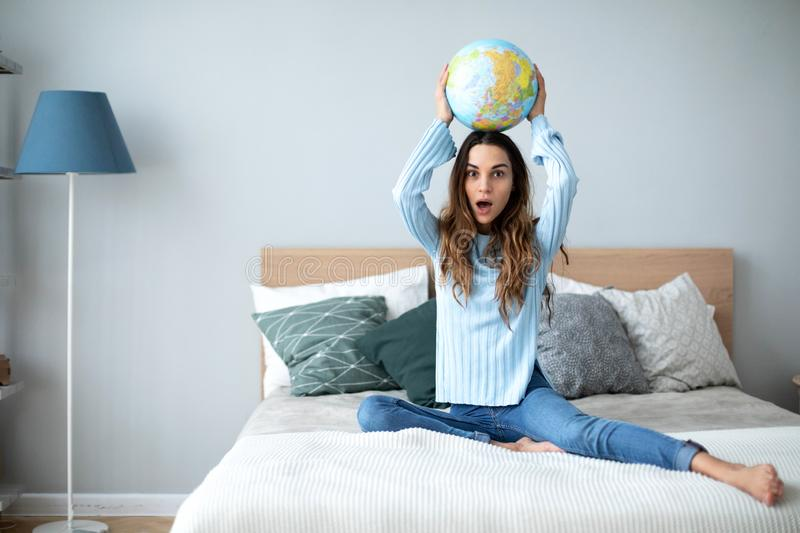 Young woman with globe model of the world at home royalty free stock images
