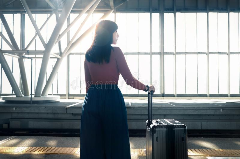 Travel Concept. Young Woman Waiting with Suitcase on the Platform at the Railway Station royalty free stock photos
