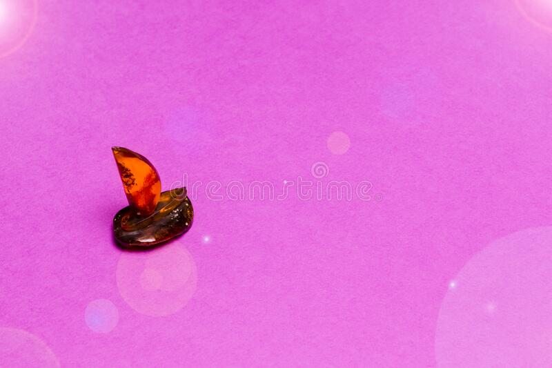 Travel Concepts. Scale Model of Artistic Amber Sail Boat Placed Over Pink Background stock photo