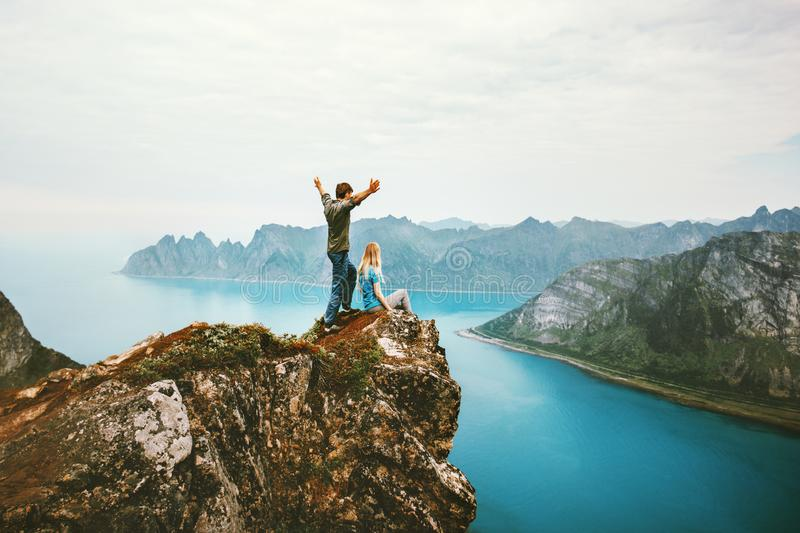 Travel couple enjoying view together on cliff edge in Norway. Men and women family healthy traveling lifestyle summer vacations outdoor success friendship happy stock photos